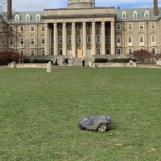Small Robot Scuttling Across Old Main Lawn Is an Electric Mower